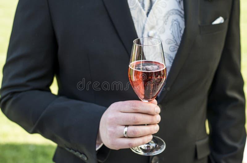 Выхольте держать стеклянное игристое вино wedding красное кольцо крупного плана костюма шампанского стоковые фото