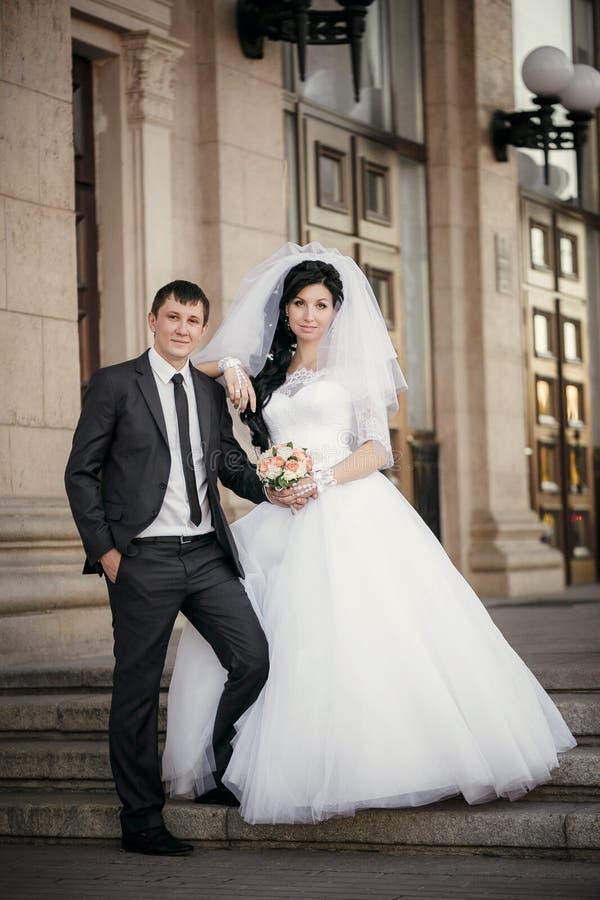 Выхольте и невеста с букетом свадьбы около белого столбца стоковое изображение