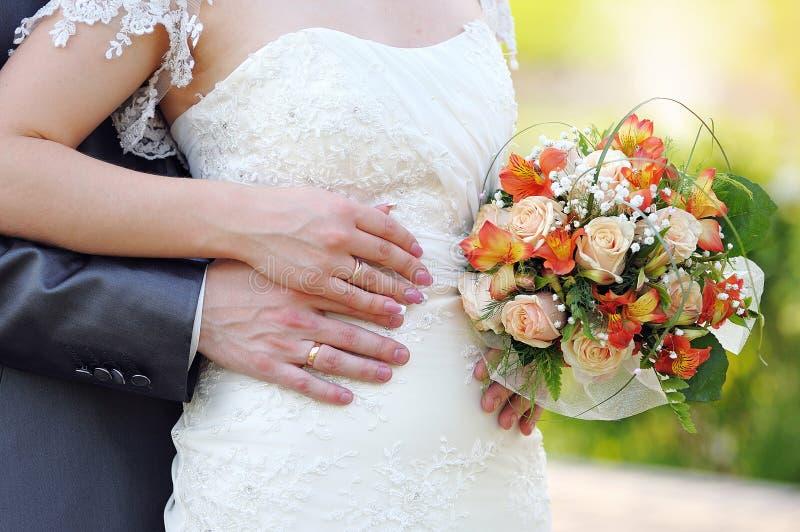 Выхольте объятия невеста, невеста держит букет свадьбы стоковые изображения