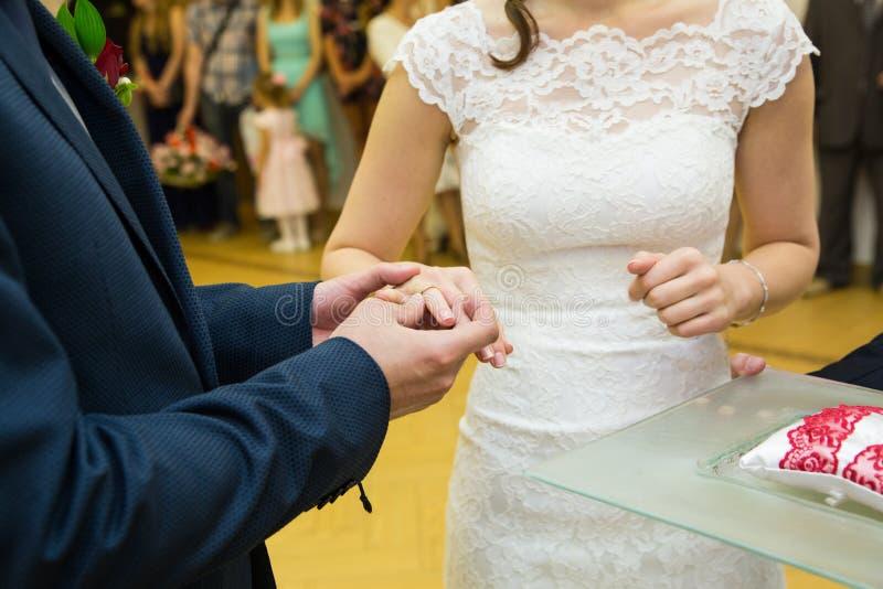 Выхольте установку золотого кольца на палец невесты во время cerem свадьбы стоковое изображение