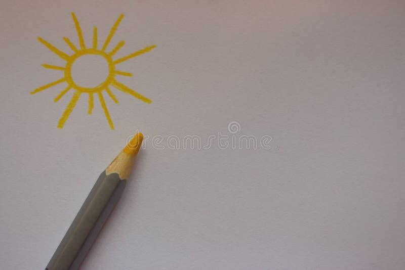 Вычерченное солнце с желтым карандашем на предпосылке белой бумаги с космосом экземпляра Изображение Солнця стоковое фото