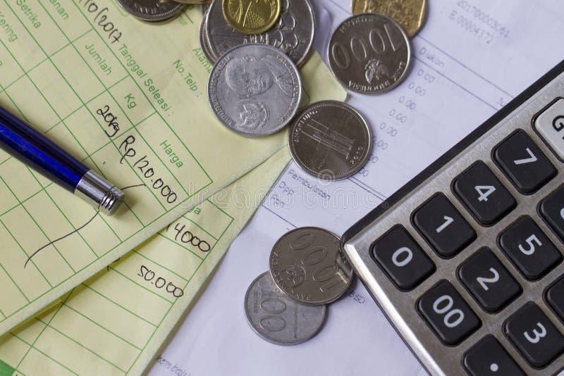 Вычисление получения оплаты с монетками рупии Индонезии и доллара Сингапура, калькулятором и фактурами в взгляд сверху/плоском по стоковое изображение rf