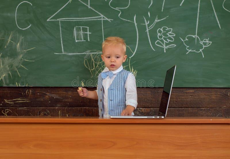 Вычислительная технология для школьного образования Оборудование ноутбука пользы маленького ребенка вычисляя на доске класса Прим стоковое изображение rf