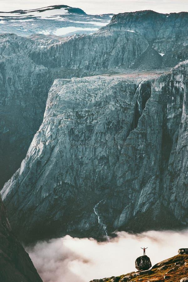 Вычислите по маcштабу показывать человека ландшафта на валуне и скалистых горах стоковая фотография rf