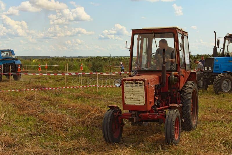 Вычисляйте пилотируя конкуренцию на поле Красный старый трактор ждет его попытка Следующий участник готов начать стоковое фото