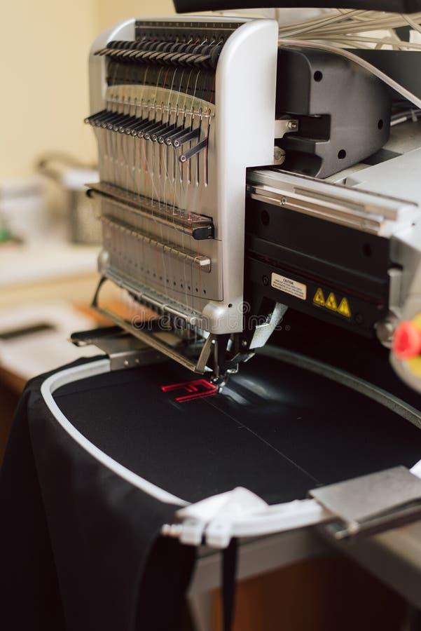 Вышивая текст на швейной машине на промышленном масштабе машина вышивает письму f на ткани стоковое изображение