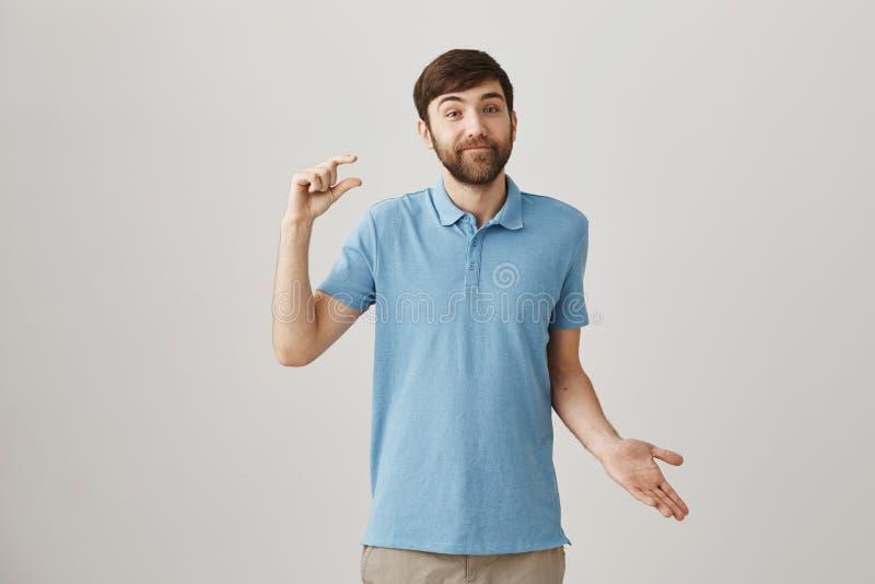 Вы должны быть счастливы даже о малых вещах Портрет милого бородатого кавказского парня показывая малые жест или формировать стоковая фотография