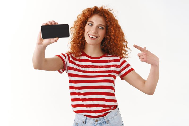 Вы должны попробовать Дисплей мобильного телефона шикарного смартфона удерживания девушки redhead курчавого горизонтальный указыв стоковое изображение