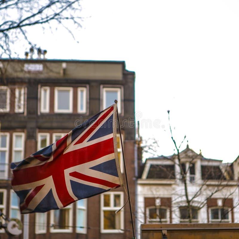 Выдержанный флаг британцев против традиционных зданий стоковая фотография rf