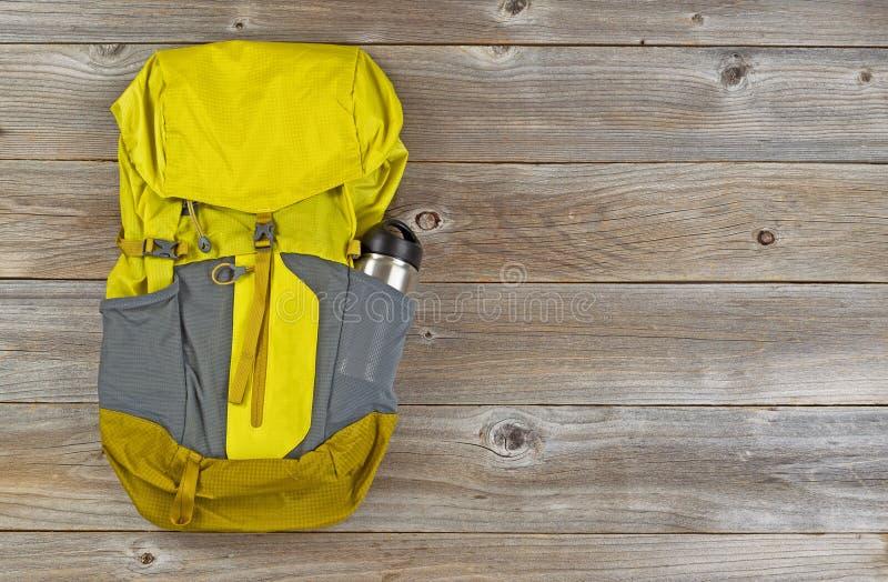 Выдержите рюкзак доказательства для пешего туризма на деревенских деревянных досках стоковое фото