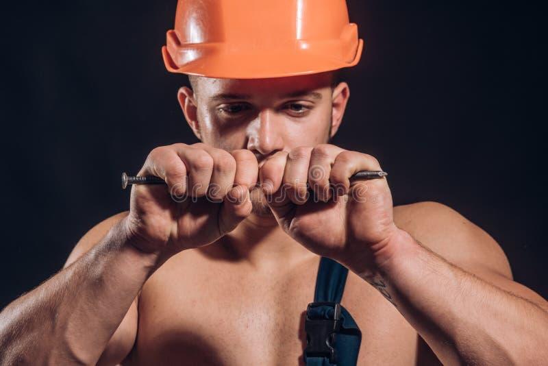 Вы можете положиться дальше Сильный человек с мышечными оружиями Мышечный ноготь загиба человека Рабочий-строитель или построител стоковая фотография