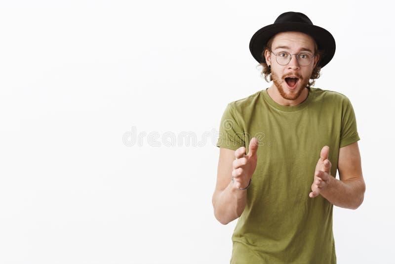 Вы не верили бы Харизматический возбужденный и изумленный красивый европейский мужчина с бородой в стеклах и описывать шляпы стоковое фото