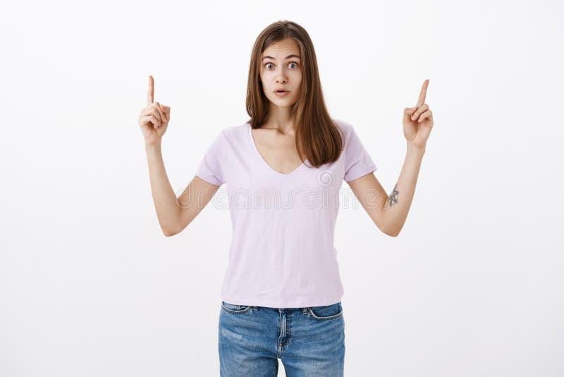 Вы никогда не верите какая девушка увидела Портрет изумленной оглушенной девушки в случайной футболке v-шеи поднимая оружия указы стоковое фото rf