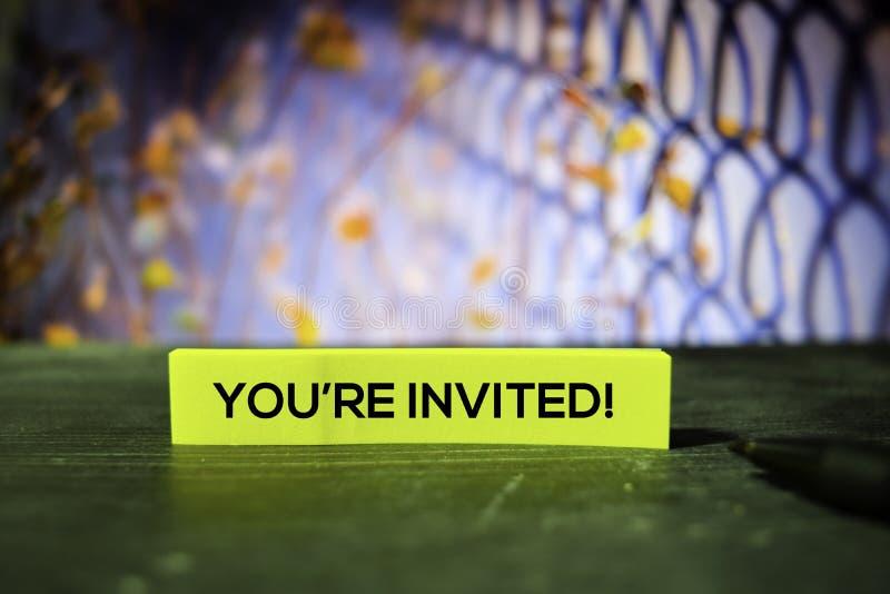 Вы приглашены! на липких примечаниях с предпосылкой bokeh стоковые изображения