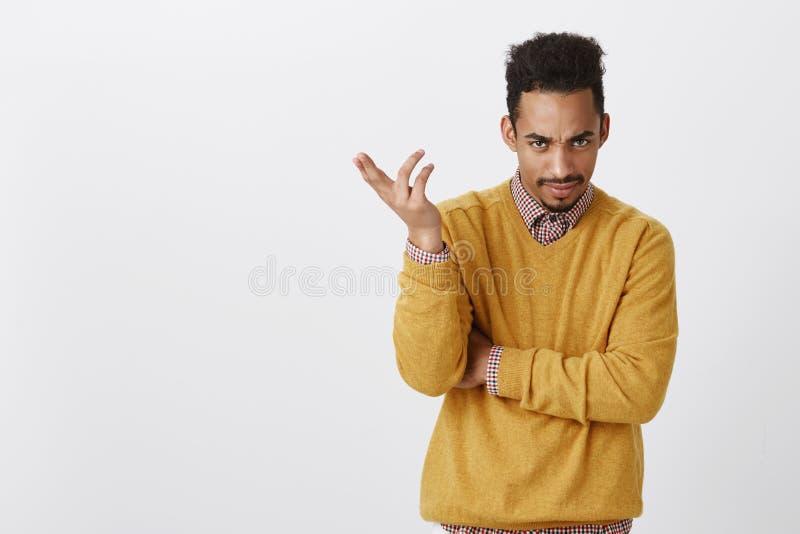 Вы тупые Портрет надоеданного симпатичного мужчины с афро стрижкой в желтых одеждах, показывать, выражая запутанность стоковое изображение