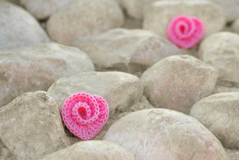 2 вязали сердца крючком закручивают в спираль на предпосылке бежевых камней стоковая фотография rf