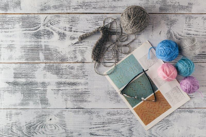 Вязать иглы и пряжа на деревянной предпосылке/естественных шерстях вяжут стоковая фотография