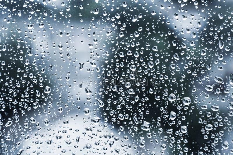 Влажное стекло с капельками, синяя предпосылка фото стоковое изображение