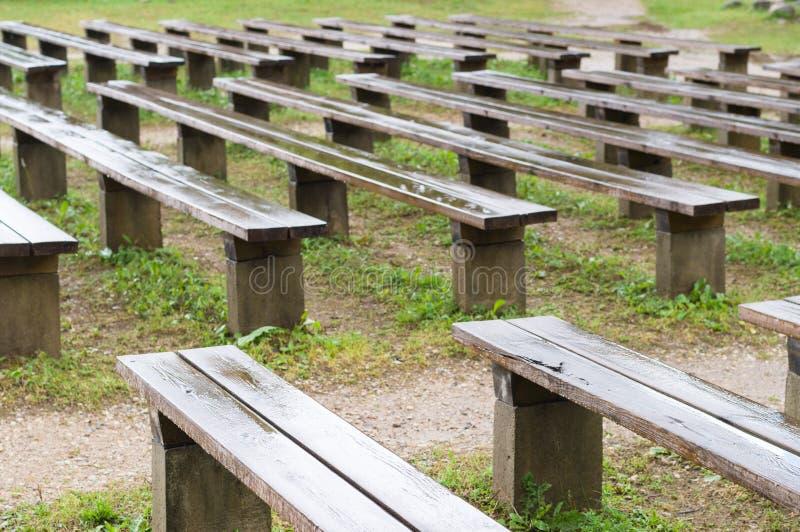 Влажные деревянные скамьи после дождя в парке стоковая фотография