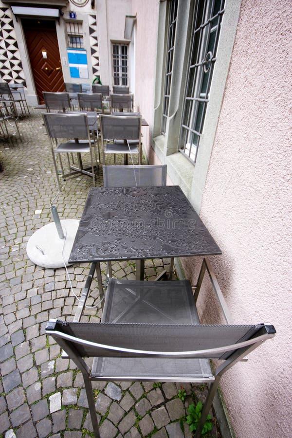 Влажные таблицы и стулья в дождливом дне на кафе мостоваой стоковое фото