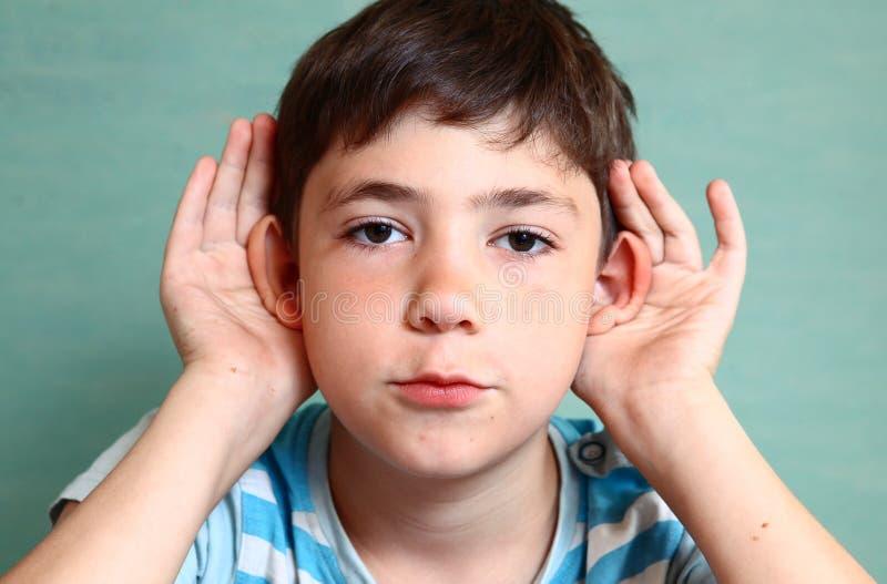 Владение мальчика Preteen красивое его слышит изолированный на сини стоковые фотографии rf