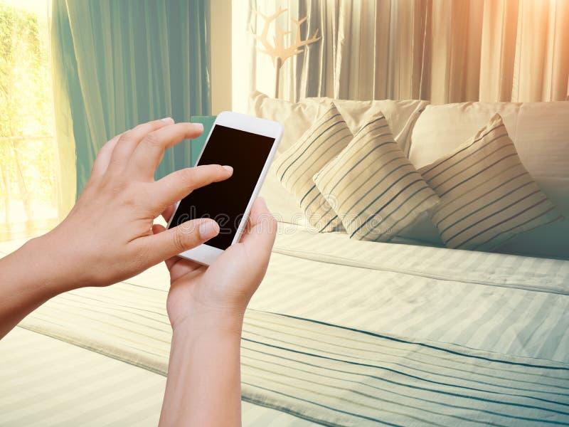 Владение руки женщины и телефон экрана касания умный на винтажной спальне стоковые изображения