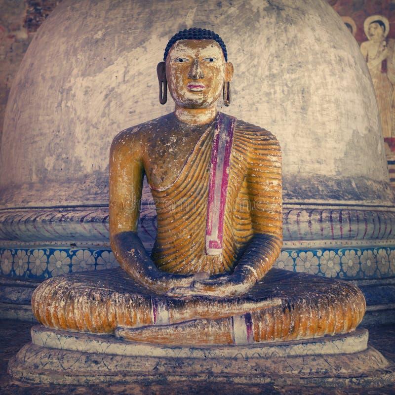 В виске пещеры Dambulla Старая затрапезная статуя Будды стоковые изображения rf