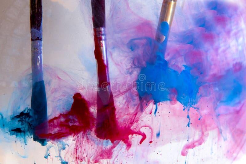 В воде 3 кисти с голубыми и красными красками стоковые изображения rf