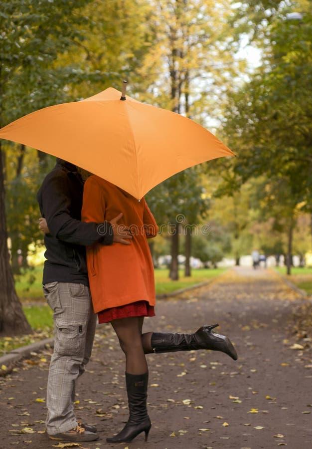 В влюбленности пары стоя под зонтиком в осени паркуют на моле стоковая фотография rf