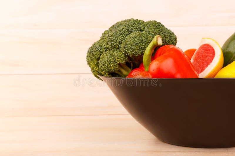 В глубокой плите, овощи и цитрусовые фрукты Брокколи, перец, лимон и грейпфрут indoors стоковое фото rf