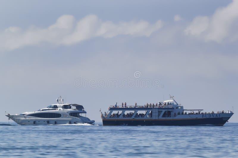 В заливе Budva прогулочный катер проходит яхтой стоковое изображение rf