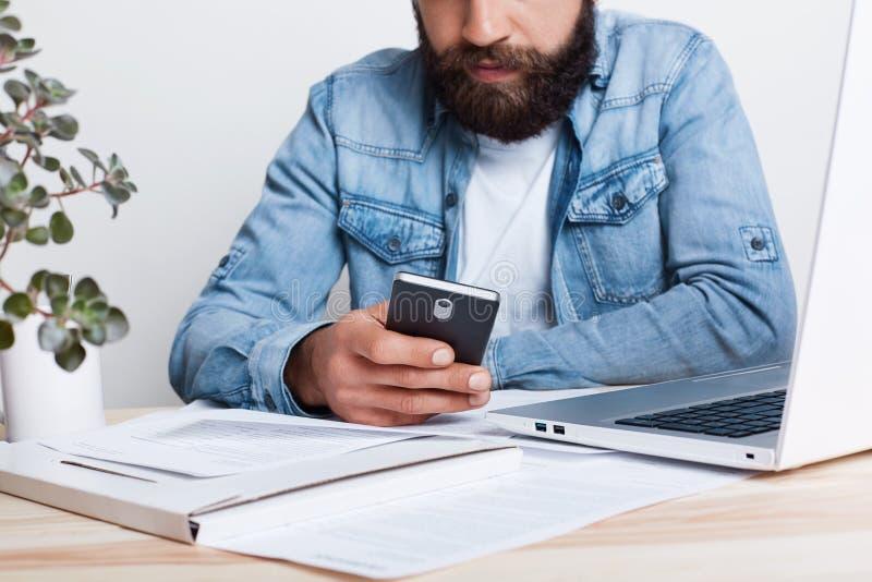 Влияние фильма Портрет бородатого человека в smartphone рубашки демикотона hoding в его руке пока работающ с документами в офисе  стоковые изображения rf