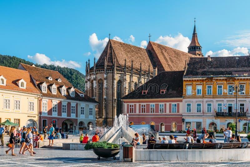 В квадрате Piata Sfatului совету Brasov обнаружьте местонахождение муниципальному жилому дому, старому городку и черной церков стоковое фото