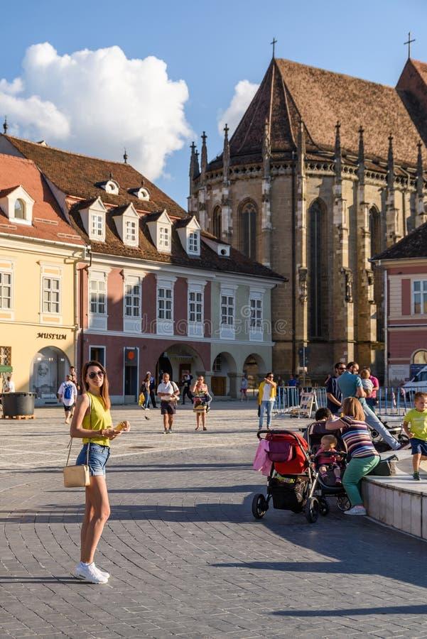 В квадрате Piata Sfatului совету Brasov обнаружьте местонахождение муниципальному жилому дому, старому городку и черной церков стоковая фотография