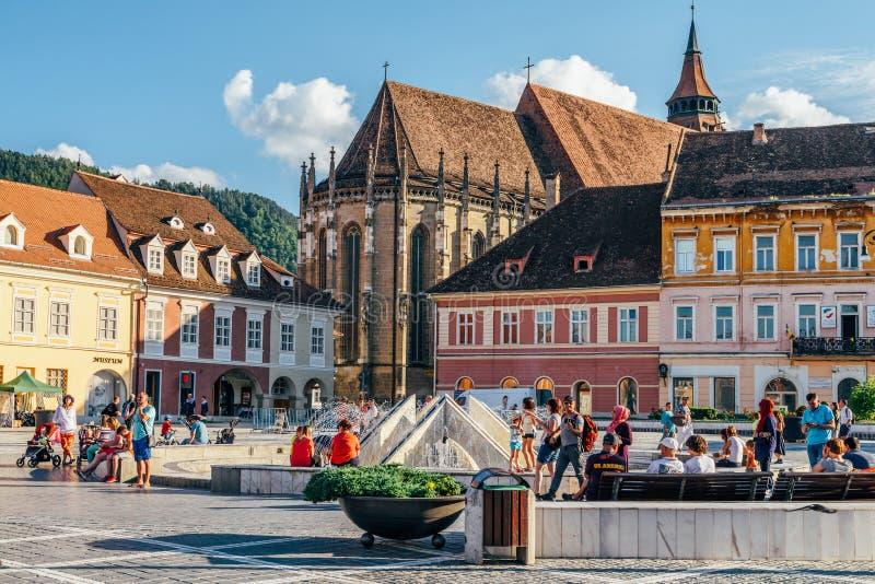 В квадрате Piata Sfatului совету Brasov обнаружьте местонахождение муниципальному жилому дому, старому городку и черной церков стоковая фотография rf