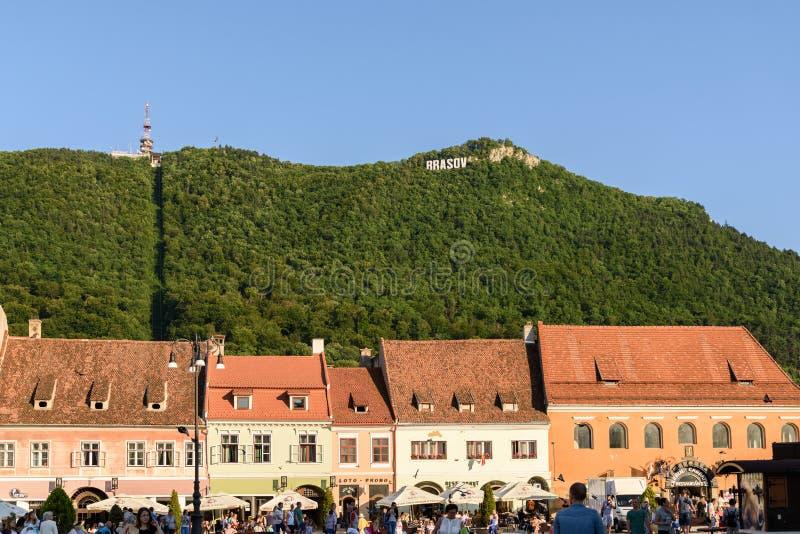 В квадрате Piata Sfatului совету Brasov обнаружьте местонахождение муниципальному жилому дому, старому городку и черной церков стоковое фото rf