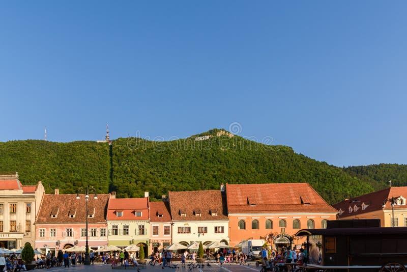 В квадрате Piata Sfatului совету Brasov обнаружьте местонахождение муниципальному жилому дому, старому городку и черной церков стоковые изображения