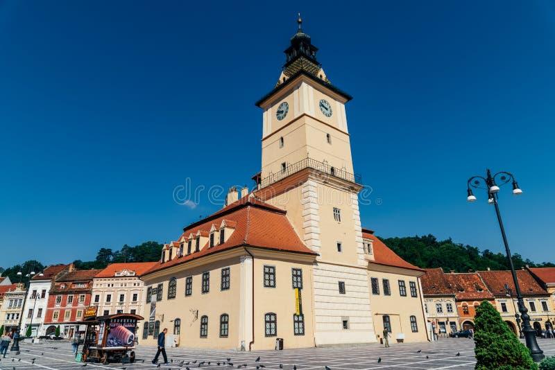В квадрате Piata Sfatului совету Brasov обнаружьте местонахождение муниципальному жилому дому, старому городку и черной церков стоковые фотографии rf