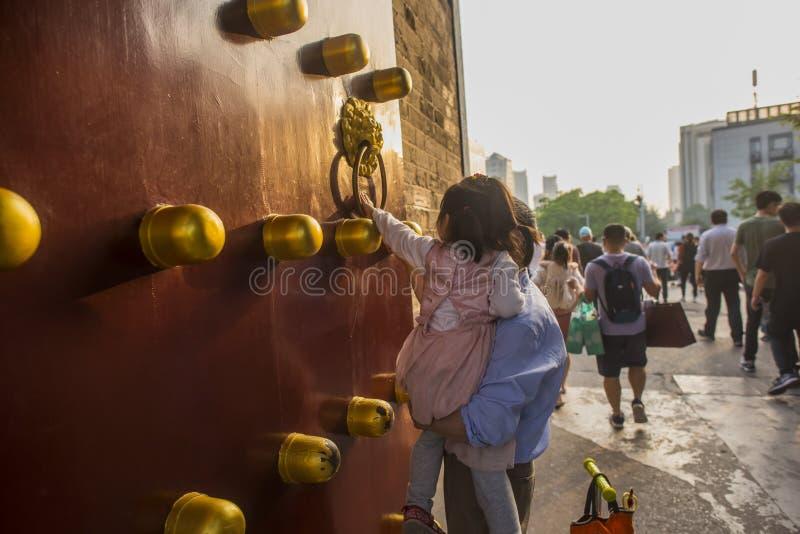 В красивом заходе солнца, старик держит маленькую девочку, маленькая девочка касается латунному кольцу на базальте стоковая фотография