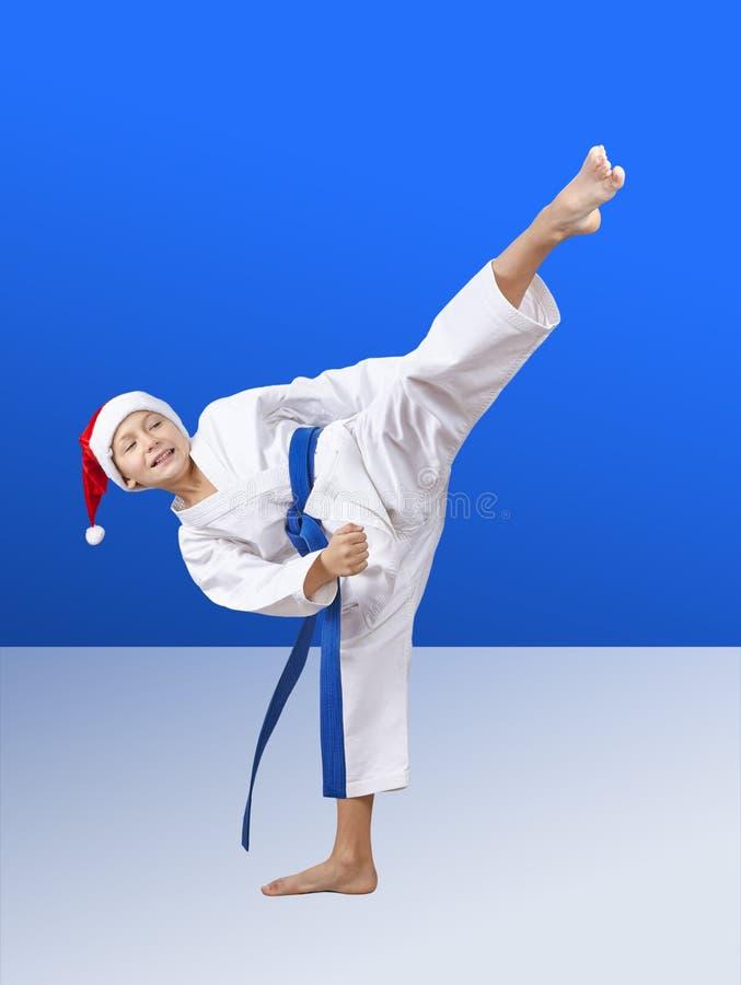 В крышке Санта Клауса спортсмен бьет пинок локомотивного депо стоковое изображение rf