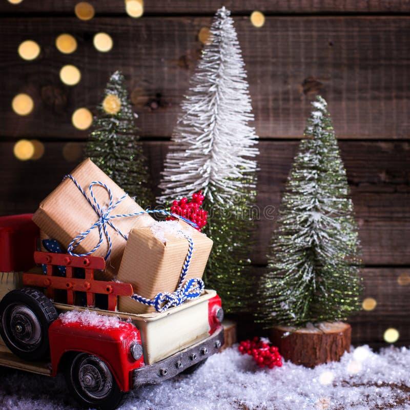 В оболочке коробки в красных автомобиле и елях на достигшем возраста деревянном backgroun стоковое изображение