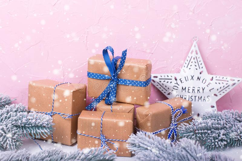 В оболочке коробки с настоящими моментами, ветвями ели и звездой рождества на белой текстурированной предпосылке против розовой с стоковые фотографии rf