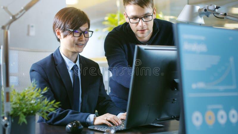 В офисе бизнесмен сидит на его столе имеет обсуждение с h стоковая фотография rf
