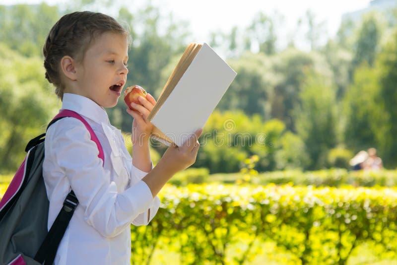 В парке, в свежем воздухе, школьница читает книгу и ест яблоко, место для надписи стоковые изображения rf