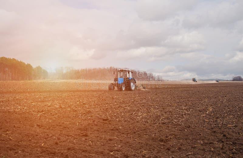 В предыдущем, утро весны, из-за древесины яркое солнце восходит Трактор идет и вытягивает плужок, вспахивая поле перед Ла стоковые фотографии rf