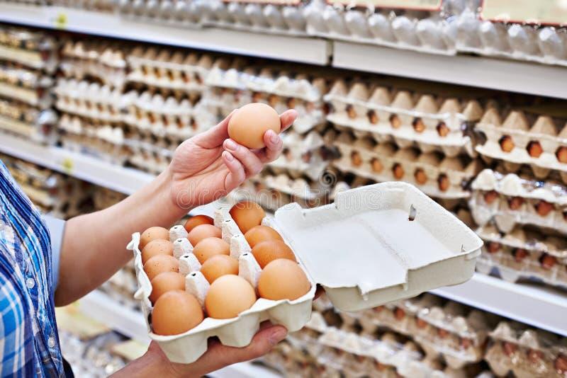 В руках женщины упаковка eggs в супермаркете стоковое изображение