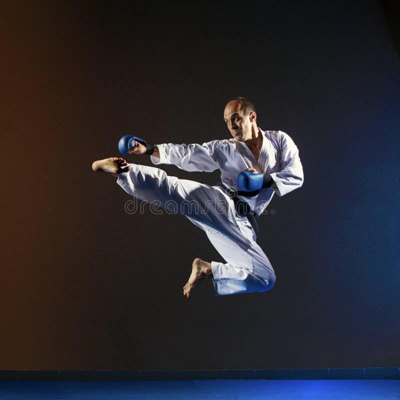 В спортсмене высокого прыжка в karategi удары пинают ногу стоковая фотография