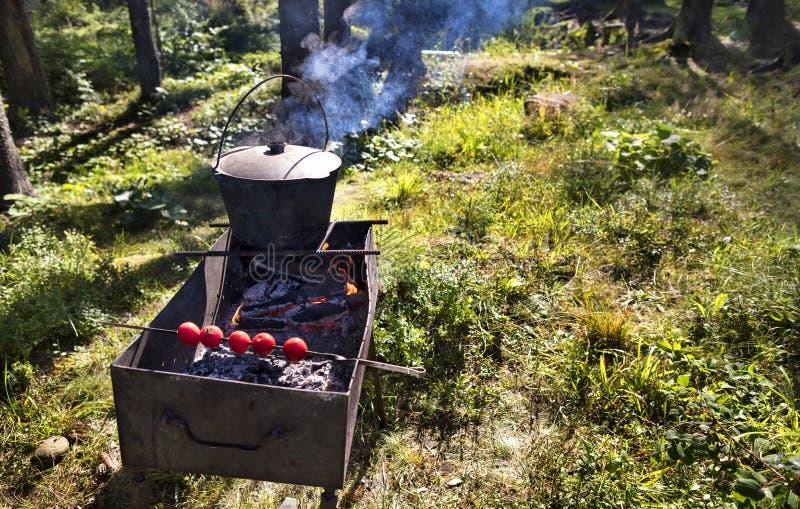 В старом котле на барбекю варя кашу против леса освобождаясь в полдень стоковые фотографии rf