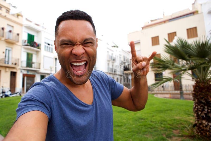 В стиле фанк молодой африканский человек делая рок-н-ролл руку подписать и принимая selfie стоковое изображение