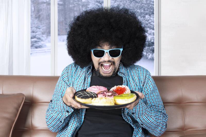 В стиле фанк человек держа donuts стоковые изображения rf